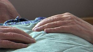 Vanhus makaa kädet rinnalla.