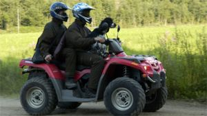 Nuori mies ajaa mönkijällä, kaveri ja koira ovat kyydissä.