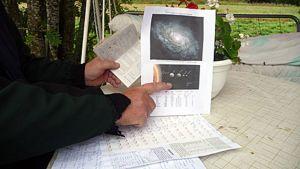Käsi pitää kalenteria ja sormi osoittaa planeettakarttaa