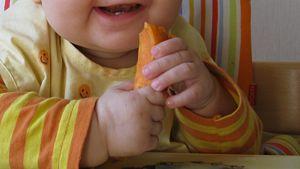 Pala bataattia vauvan käsissä