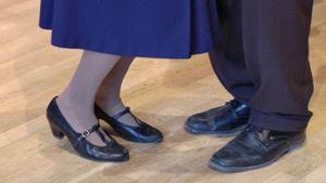 Eläkeläiset tanssimassa. Kuva iäkkään naisen ja miehen kengistä.