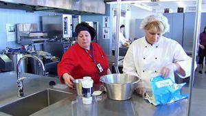 Punatakkinen naisesimies neuvoo valkotakkista naista leivonnassa, leivontavälineitä ja -tarvikkeita suurkeittiön teräksisillä tasoilla.