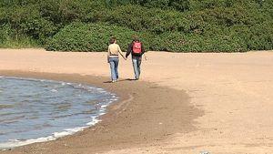 Nuori mies ja nuori nainen kävelevät käsikkäin kesäisellä hiekkarannalla auringonpaisteessa.