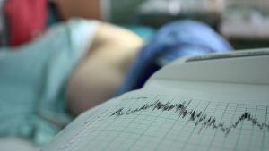 Nainen makaa synnytyssängyssä, kone piirtää paperille käyrää.