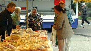 Torimyyjä kauppaa leivonnaisia asiakkaille Karkkilan torilla.
