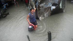 Nainen kahlaa polvia myöten tulvavedessä