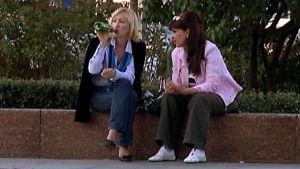 Kaksi naista nauttimassa alkoholipitoisia virvokkeita puistossa