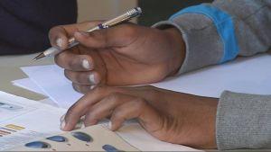 Mustekynä oppikirjaa lukevan pakolaisen kädessä.