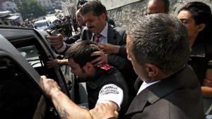 Turkin poliisi taluttaa väkisin kengänheittäjä Selcuk Ozbekia autoon välikohtauksen jälkeen.