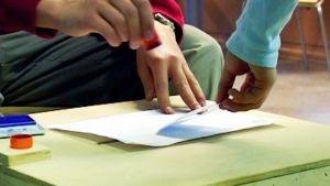 Nuoret leimaavat äänestyslipuketta.