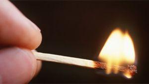 palava tulitikku kädessä