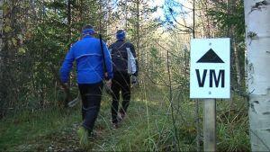 Kaksi miestä kulkee polkua, jonka varrella Vaarojen maratonin opaste.