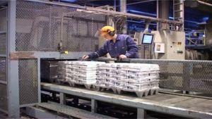 Kuvassa on valmiita sinkkiharkkoja, jotka kulkevat liukuhihnalla. Työntekijä valvoo toimintaa.