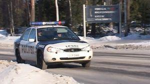 Kuvassa ajaa Ford Mondeo-merkkinen poliisiauto, tie on luminen ja taustalla on mäntymetsää.