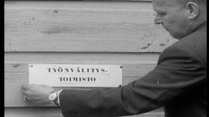 Mies asentaa työnvälitystoimiston kylttiä seinään 1960-luvulla