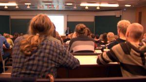 yliopisto-opiskelijoita luennolla.
