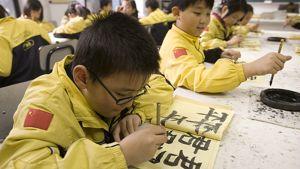 Yksityiskoulun lapsioppilaat kirjoittavat musteella.