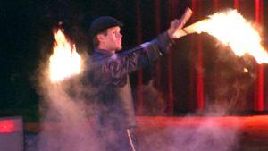 Sirkusakrobaatti temppuilee tulen kanssa.