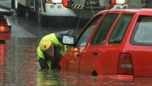 Mies työntää puolittain vedessä olevaa autoa.