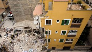 Pelastusmiehistö raivaamassa sortuneen talon raunioita