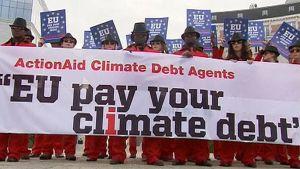 """Punaisiin pukuihin ja aurinkolaseihin pukeutuneita mielenosoittajia seisoo rivissä Brysselissä. Pitävät käsissään lakanaa, jossa lukee """"EU pay your climate debt""""."""