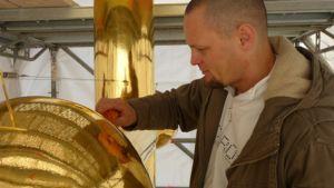Kultaajamestari Harri Virtanen kiillottaa Tuomiokirkon ristin kultausta.