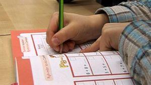 Koululainen laskee laskuja matematiikan kirjaan.