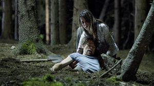 Charlotte Gainsborough yrittää nostaa maahan kaatunutta Willem Dafoeta sammaleisessa metsässä