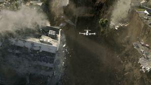 Lentokone kiitää pakoon romahtavia pilvenpiirtäjiä.