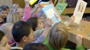 lapset hakevat innoissaan lukemista kirjastossa