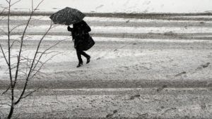 Räntäsateessa sateenvarjon kanssa kulkeva nainen.