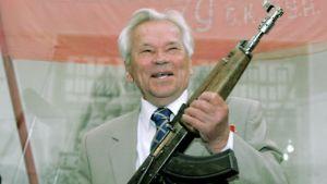 Mihail Kalashnikov poseeraa ensimmäisen rynnäkkökiväärinsä kanssa