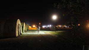 Guantanamon vankileiri pimeässä lyhtypylväiden valossa. Nukkumista varten pystytettyjä telttoja.