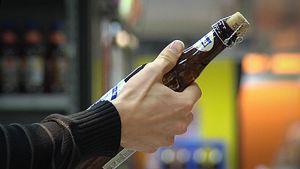 Asiakas tarkastelee olutpulloa kaupassa. Olutpullo kädessä.