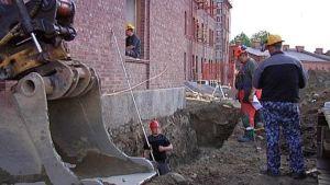 kaivinkoneen kauha ja työmiehiä arkeologisilla kaivauksilla