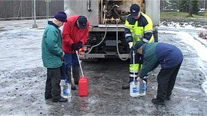 Asukkaat hakevat säiliöautosta vettä pulloihin.