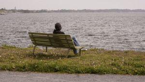 Mies istuu yksin penkillä meren rannalla.