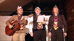 Kolme miestä laulaa ja soittaa.