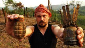 Riku Rantala poseraa kameralle toisessa kädessään käsikranaatti, toisessa ruosteinen miina.