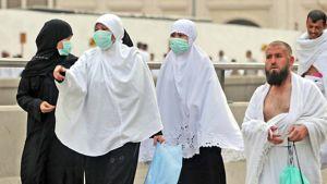 Kolme naista on pukeutunut burkhaan ja hengityssuojaimiin. Kaksi oikealla olevaa miestä kulkevat ilman suojaimia.