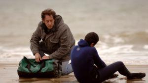 Kaksi miestä harmaalla tuulisella rannalla, toinen kyyhöttää märkäpuvussa, toinen polvillaan vieressä ison urheilukassin kanssa