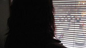 Masentunut nainen katsoo ikkunasta ulos
