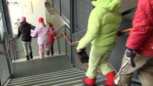 Ala-asteikäisiä oppilaita kävelee koulun portaita alaspäin.