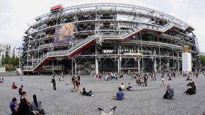 Pompidou-keskuksen rakennus. Ohikulkijoita ja ihmisiä istuu maassa edustalla.