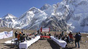 Nepalin pääministeri johtaa hallituksensa istuntoa ulkoilmassa Kalapatharissa Mount Everest -vuoren juurella. Aurinkoinen sää. Pöydillä valkeat pöytäliinat.