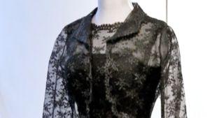 Torso, jonka päällä osa mustasta, osittain läpinäkyvästä mekosta.