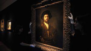 Maalaus esittää miestä kädet puuskassa. Gallerian assistentit ripustavat maalausta esille.