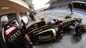 Lotuksen mustakultainen formula-auto varikolla.