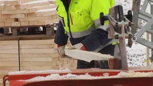 Mies sirkkelöi lautaa rakennustyömaalla.