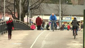 Ihmisiä kävelemässä ja pyöräilemässä sillalla Salossa.